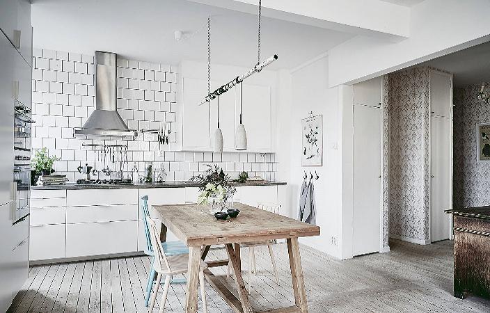 Светлая кухня со стильным дизайном и светильником.