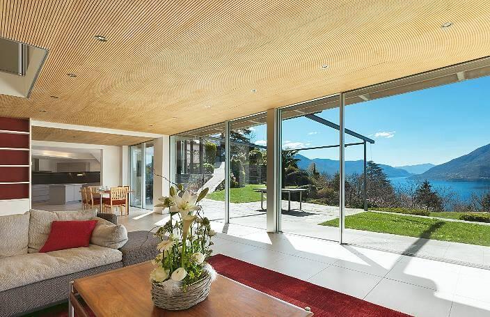 Комната с большим окном и деревянным потолком.