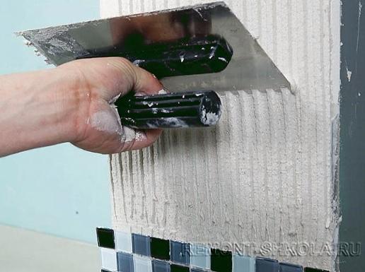 Нанесение специального белого клея для мозаики на стену