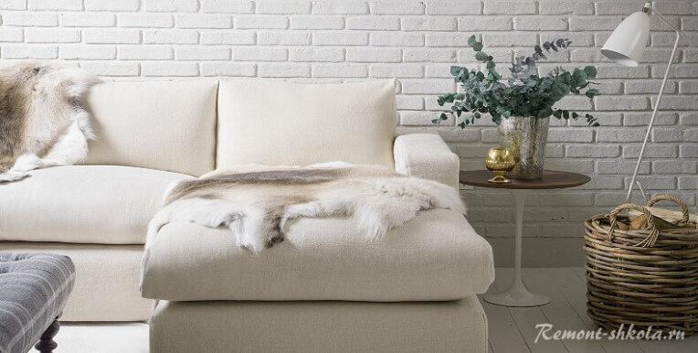 Белый диван на фоне белой кирпичной стены