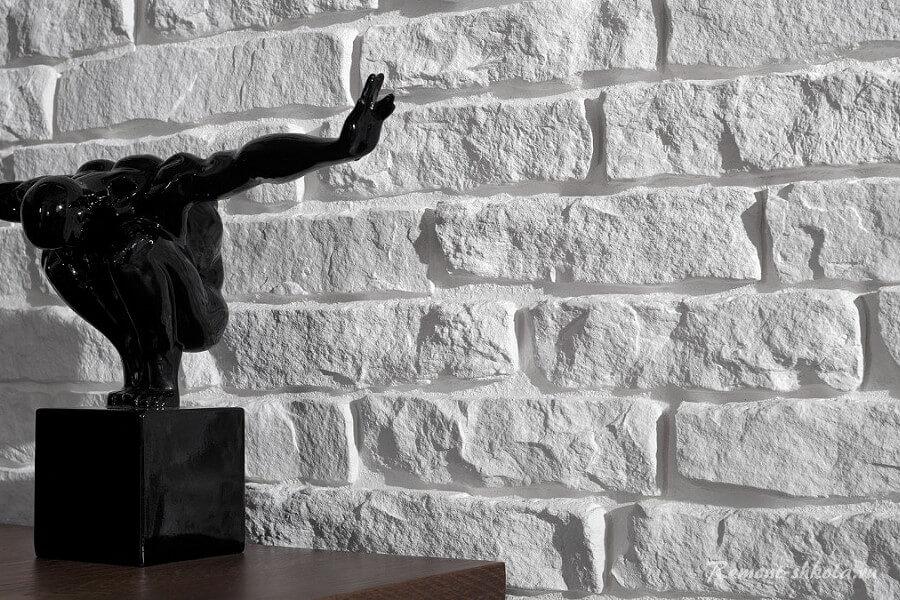 Статуэтка на фоне стены из белой гипсовой плитки