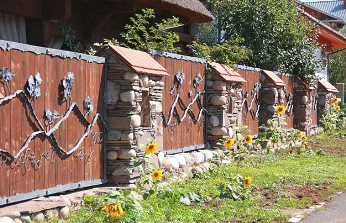 Забор из дерева и ковки с каменными столбами